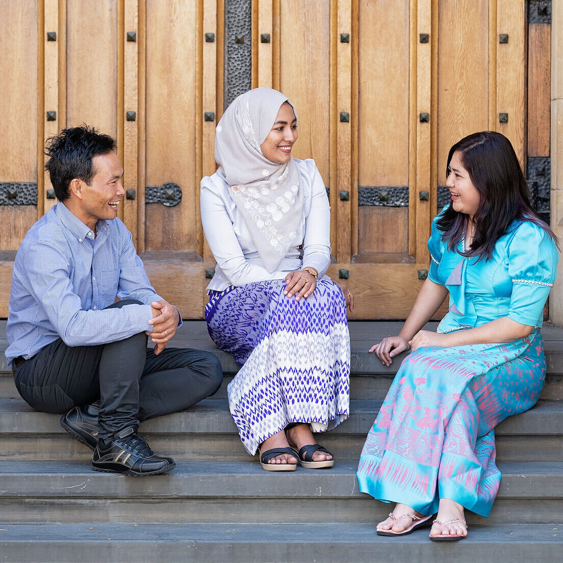 Three people sitting on steps and having a chat